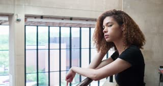College girl leaning against railing looking into distance 4k