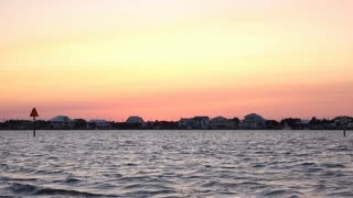 Colorful sky at sunset over ocean side houses 4k