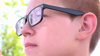 Confident boy looking into distance with cloud reflection in glasses 4k