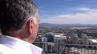 Confident businessman looking over edge of balcony upon city 4k