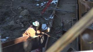 Construction worker welding on beam