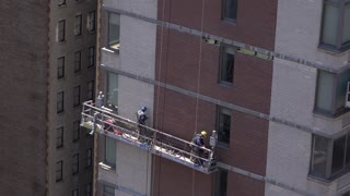 Construction workers on side of tower block in New York 4k