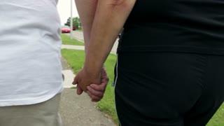 Couple holding hands walking down sidewalk