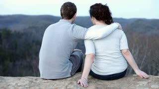 Couple Sitting on ledge looking at Forest