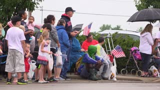 Crowd of people on sidewalk watching 4th of July parade 4k
