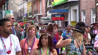 Crowded Bourbon Street on Mardi Gras people walking by