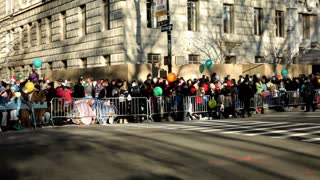 Crowds of people along fence at Macy's parade