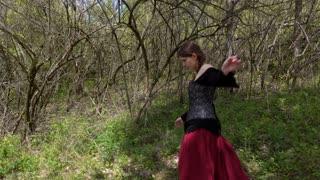 Curious Renaissance woman walking through forest 4k