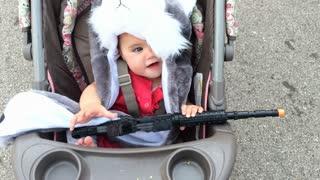 Cute kid with toy gun in stroller