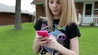 Cute teen girl texting on cell phone smiles at camera