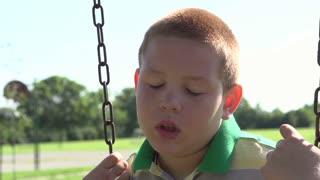 Depressed child sitting on swing