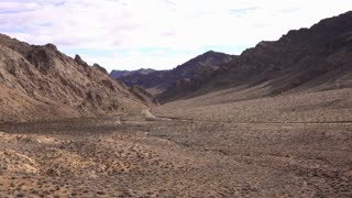 Desert valley wide view with car going down highway 4k