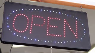 Digital open sign swaying in window
