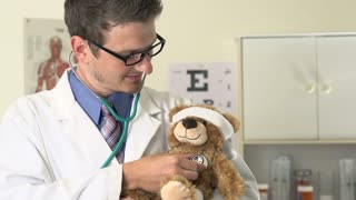 Doctor listening to heart and breathing of teddy bear