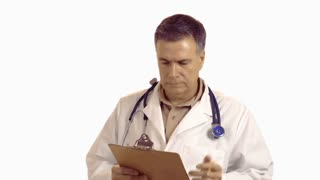 Doctor working on clipboard looks at camera