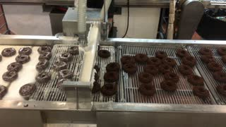 Donuts being glazed on factory production line