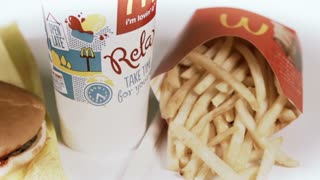 Drink, burger and fries rotating on white