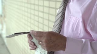 Elderly businessman looking through newspaper