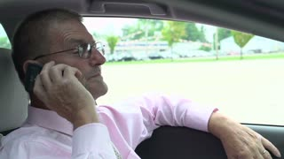 Elderly businessman sitting in car talking on cell phone
