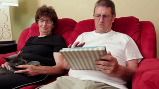 Elderly couple on couch with cat and tablet