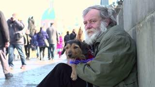 Elderly man and dog sitting on streets of Prague
