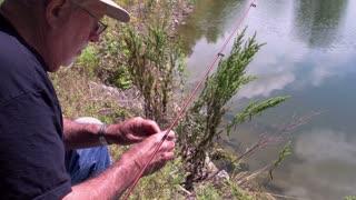 Elderly man baiting hook while fishing