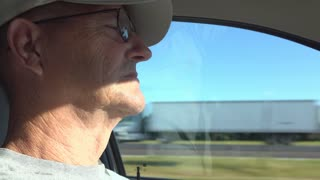 Elderly Man drives car down highway 4k