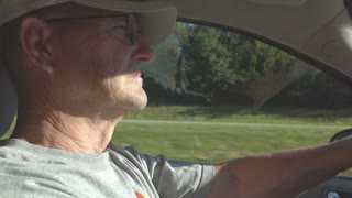 Elderly man driving car down highway in slow motion