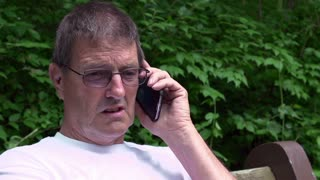 Elderly man laughing on cell phone in nature