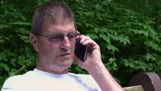 Elderly man on telephone in nature