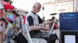 Elderly man painting in streets of Venice Italy