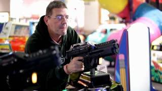Elderly man playing gun arcade game