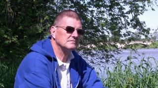 Elderly Man Removes Sunglasses