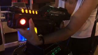 Elderly woman playing shooting arcade game