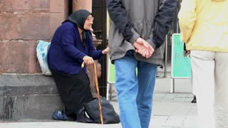 Elderly woman with hand out asking for money from pedestrians 4k