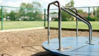 Empty merry go round spinning in kids playground