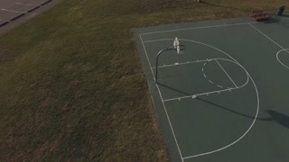 Empty outdoor basketball court pan aerial view 4k