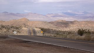 Empty road going through desert and mountains 4k