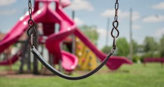 Empty swing at playground swaying in the wind 4k