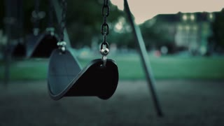 Empty swing in park during evening hours with no children 4k