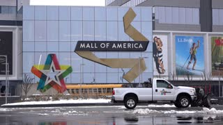 Entrance to the Mall of America with snow plows cleaning parking lot 4k