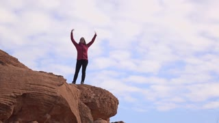 Exciting girl dancing on edge of mountain rock 4k