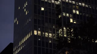 Exterior of office with lit windows at night 4k