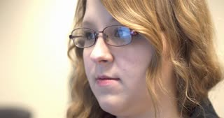 Face of young girl with glasses looking at computer monitor 4k