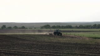 Farmer plowing land with tractor in summer
