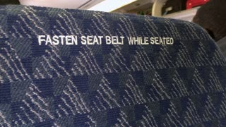 Fasten seat belt on the back of head rest in airplane