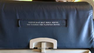 Fasten Seat belt while seated sign on back of airplane chair 4k