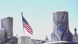 Father headstone at cemetery with flag blowing in wind 4k