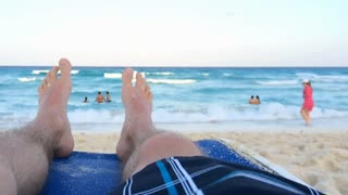 Feet of male sitting on beach shore by ocean slow motion 720p