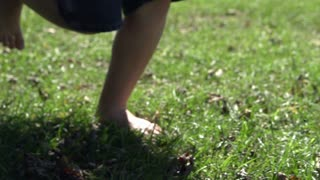 Feet running in grass tracking shot